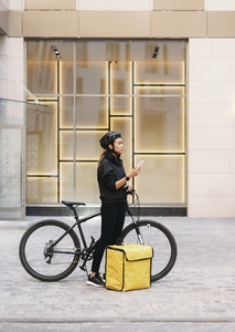 Side view female messenger standing outdoors with bicycle and thermal backpack holding a smartphone looking for a customer address