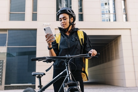 Courier with bike delivering food  Young courier checking delivery address on smartphone