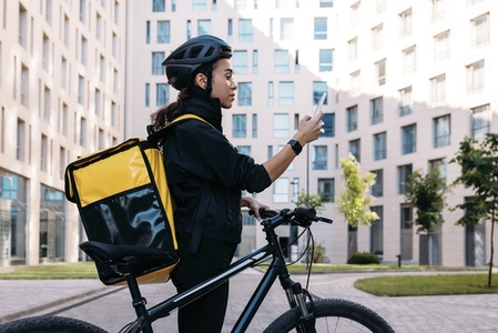 Side view of delivery woman with backpack looking at smartphone while standing in the city against apartment building