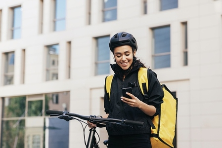 Female courier in cycling helmet with bicycle in the city  Smiling woman with thermal backpack looking at smartphone