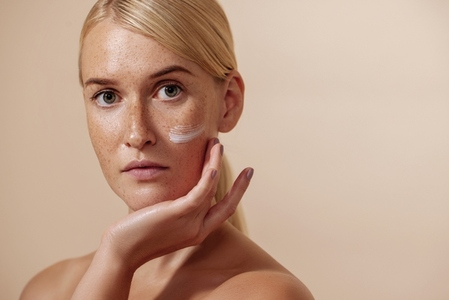 Young beautiful woman with facial cream on a cheek touching face and looking at camera