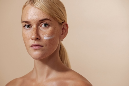 Beautiful blond woman with moisturizer on her face looking straight of a camera in studio
