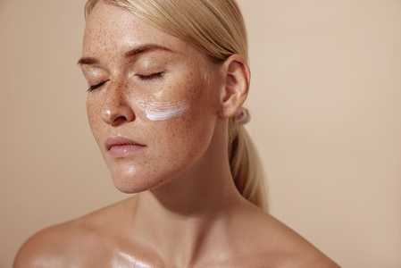 Close up of a calm and beaautiful blond woman with facial cream on a cheek against pastel background