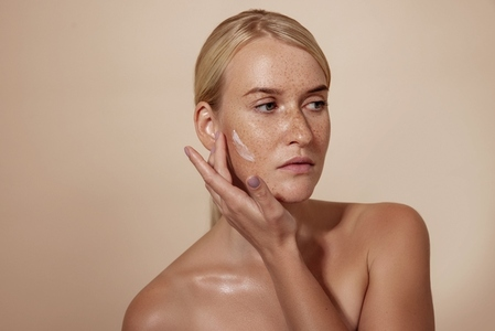 Confident woman with freckles applying anti aging cream on a cheek in studio while looking away