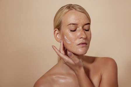 Caucasian woman applying facial moisturizer standing in studio against pastel background