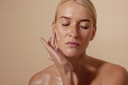 Beautiful female applying moisturizer on face in studio