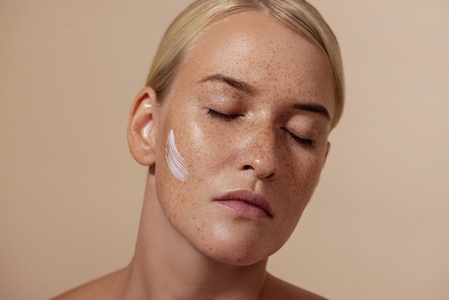 Close up portrait of beautiful caucasian woman with anti aging cream on face