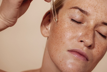 Young beautiful woman with closed eyes applying face serum with pipette