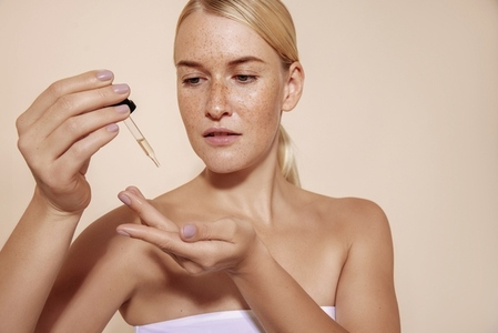 Beautiful blond woman using hyaluronic acid  Female with freckles using dropper with liquid moisturizer