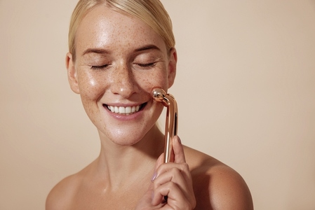 Happy woman using facial roller  Young female doing skincare routine