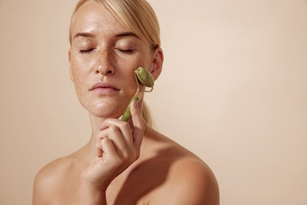 Blond woman with freckles using jade roller while standing with closed eyes against pastel background