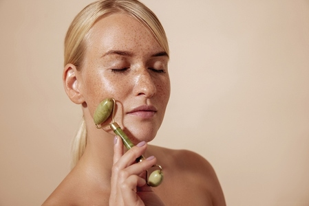 Side view of a young female with freckles massaging face with quartz roller