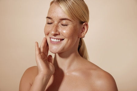 Cheerful female with blond hair massaging her cheek in studio against pastel background