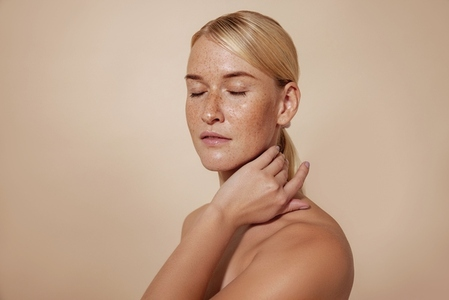 Caucasian female with freckles and blond hair standing with closed eyes massaging her neck