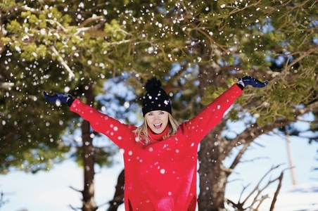 Woman throwing snowballs over her head in a snowy forest in the mountains