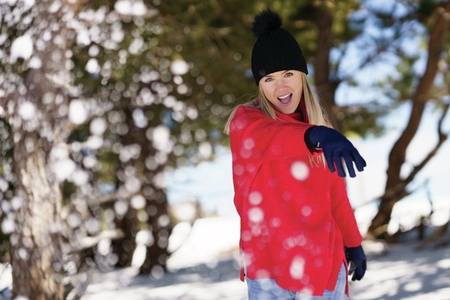 Blonde woman throwing snowballs forward in a snow covered forest in the mountains