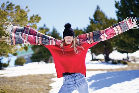 Happy young blonde woman waving her scarf in the wind in a forest in the snowy mountains