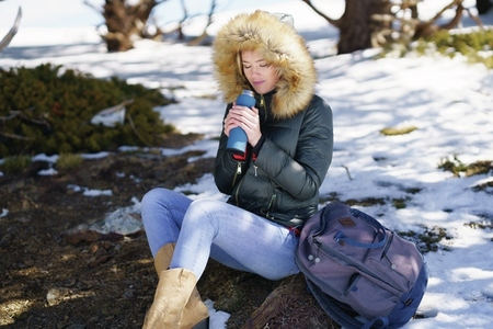 Woman drinking something hot from a metal thermos bottle sitting on a rock in the snowy mountains