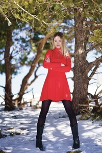 Blonde woman wearing a red dress and black stockings in the snowy mountains in winter