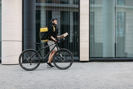 Side view of a male courier walking with a bicycle holding a package  Delivery man with thermal backpack at an office building
