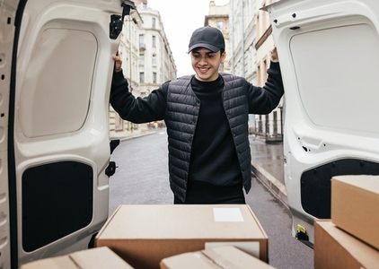 Smiling man in uniform and cap looking at cardboard boxes while standing at van trunk