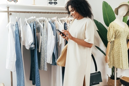 Side view of a young stylish woman holding a mobile phone at rack in small boutique