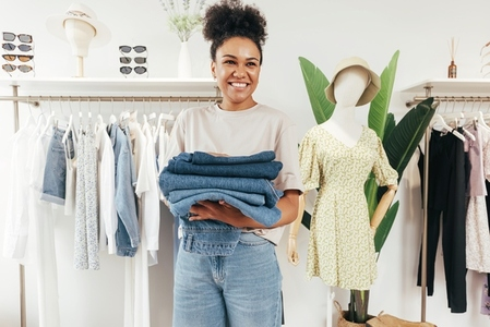 Portrait of a smiling woman in her small clothing retail shop  Happy business owner holding a pile of clothing and looking away