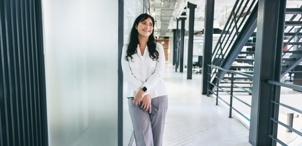 Businesswoman smiling while standing in a creative workplace