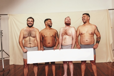 Cheerful body positivity activists holding a white banner