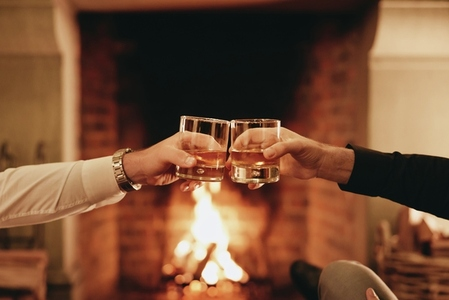 Two hands toasting with whiskey glasses