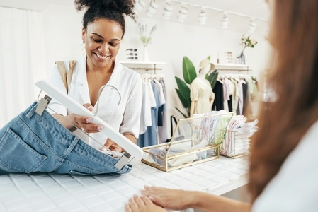 Female buyer standing at counter with jeans and looking at tag
