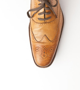 Tan brogue shoes on white backgr