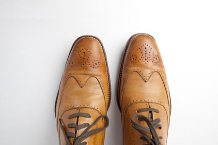 Tan brogue shoes on background