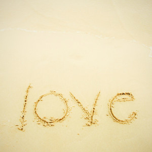 Hand written love on sand