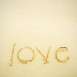 Hand written love on sand