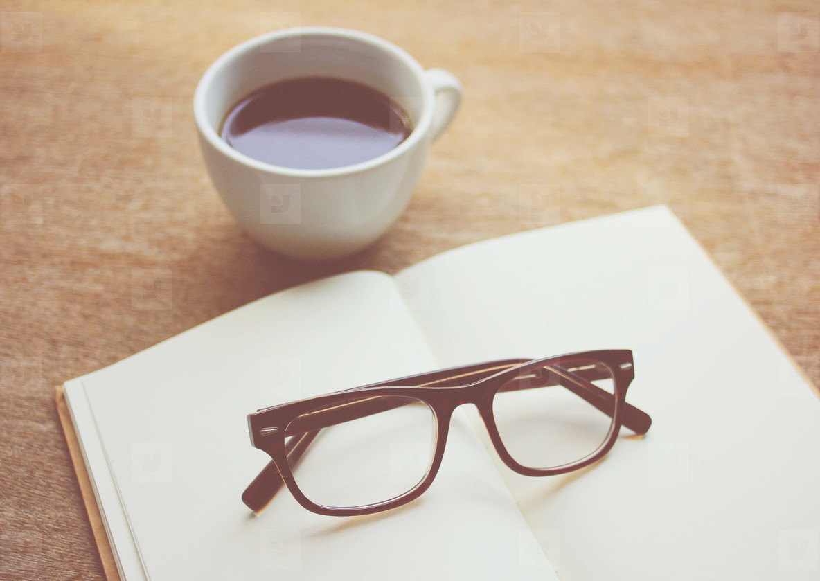 Eyeglasses on notebook and black