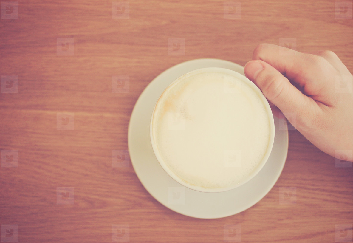 Hand holding cup of latte