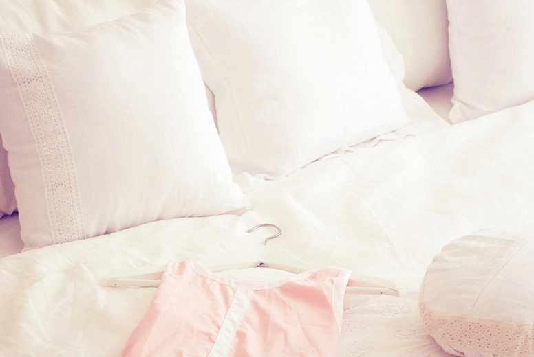 Cute dress and pillows on bed