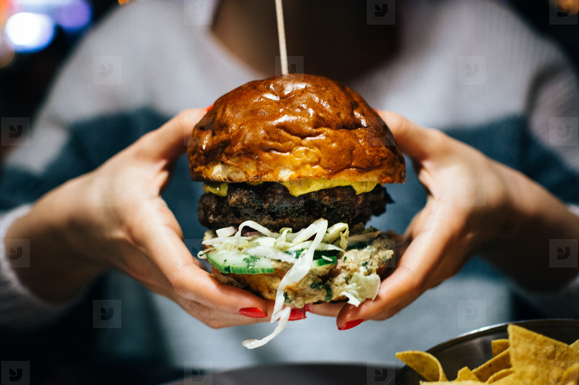 Beef burger in girl s hands