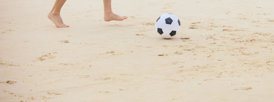 Man playing soccer ball on beach