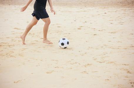 Man playing soccer ball on beach