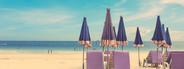 Beach chair and umbrella on sand