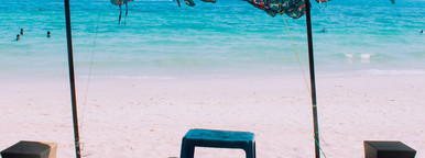 Beach chair and umbrella on sand