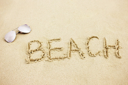 word beach on sand with sunglass