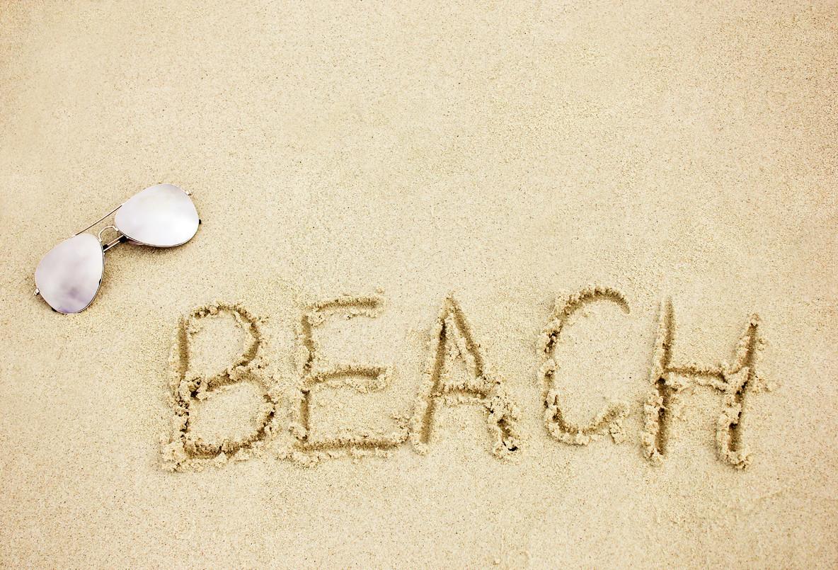 word beach on sand with sunglass