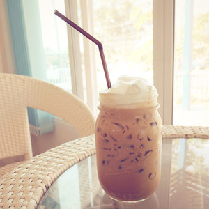 Iced coffee and straw on table