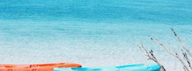 Orange and blue kayaks on sandy