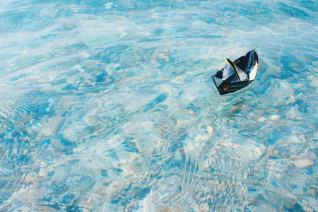 Paper boat sailing on blue water