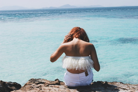 Back view of young girl on ocean