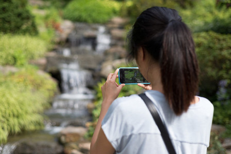 Woman taking photo of cascade